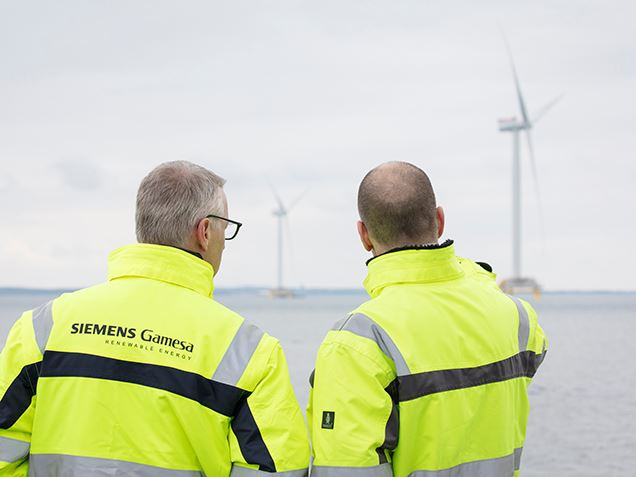 People in front of an offshore wind farm
