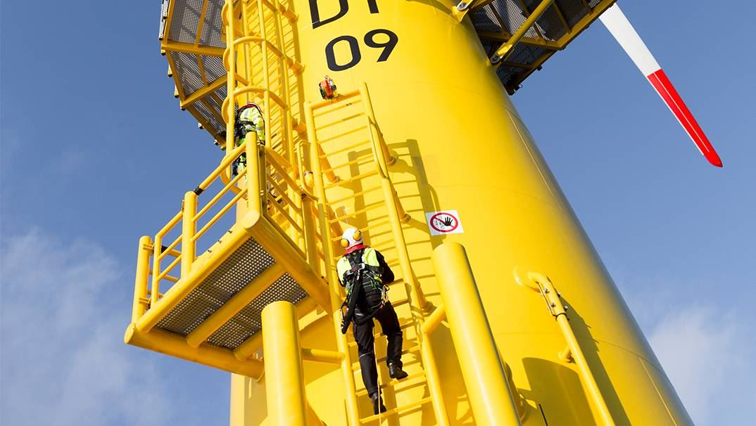 Technician climbing a wind turbine